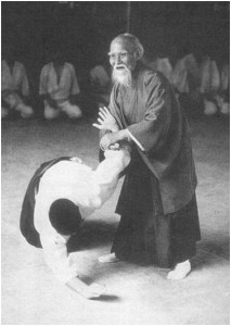 O Sensei, Morehei Ueshiba, demonstrating the minimal effort and superb control of Aikido movement in resolving conflict.